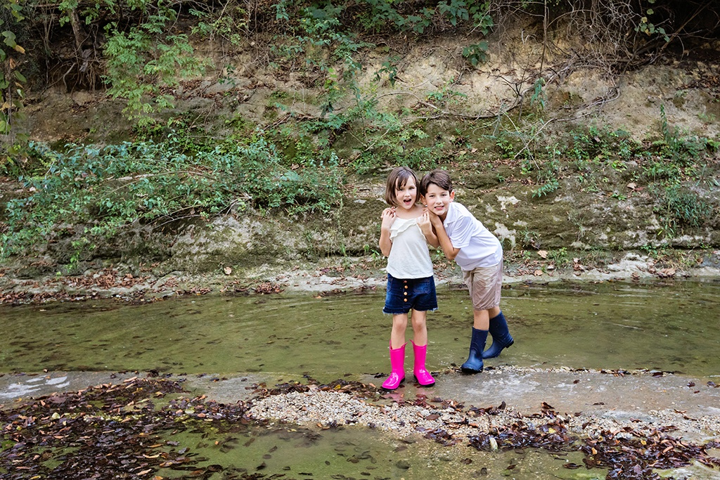kids play outside for family session in creek