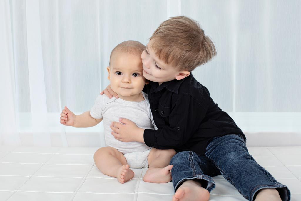 six-month old and his big brother pose in private studio for adorable and memorable photos