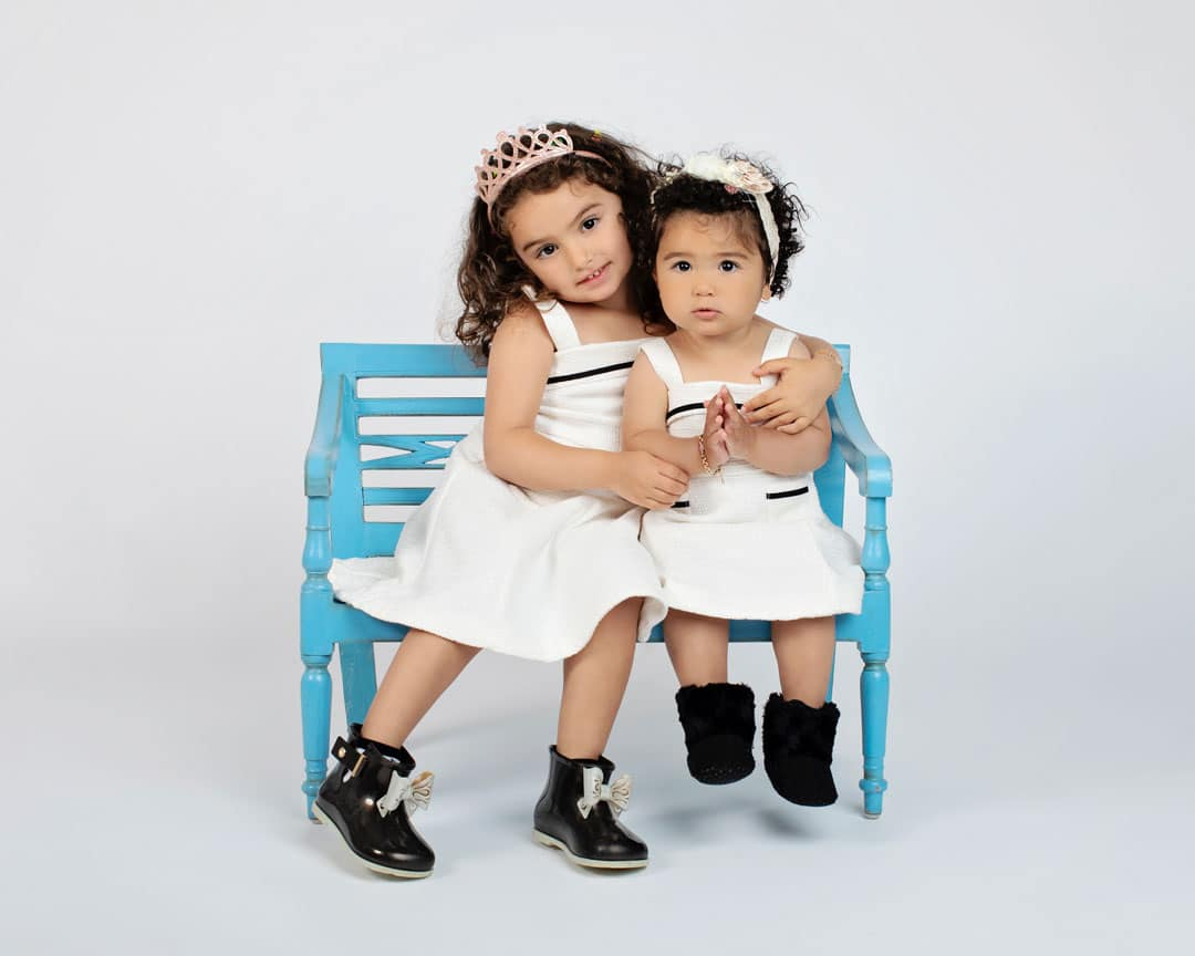 adorable sisters posing in private studio on bright blue bench
