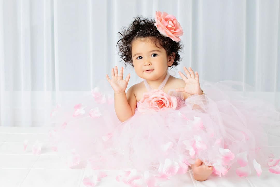 adorable little girl with detailed tutu and matching flower bow on her first birthday
