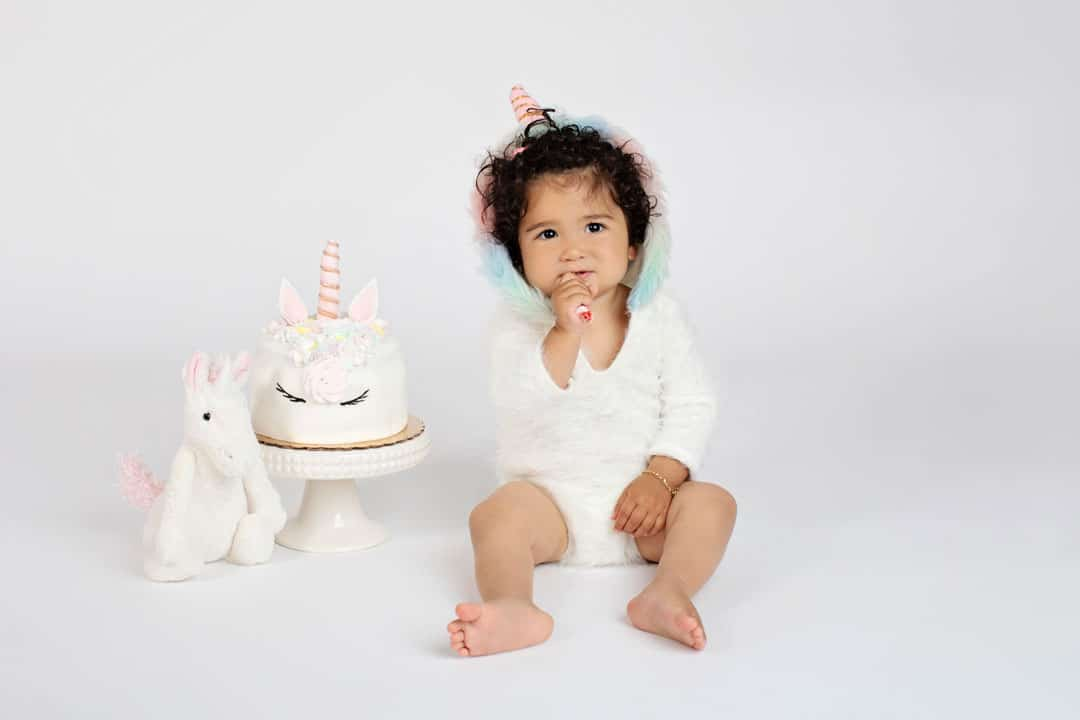 little girl with unicorn cake and matching onesie