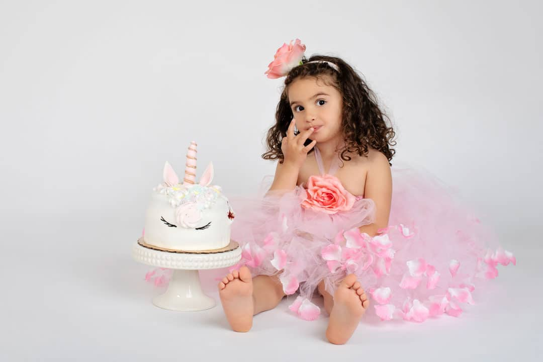 big sister posing with unicorn birthday cake
