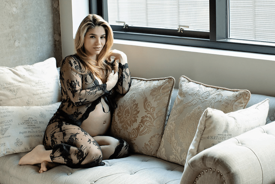 Pregnant woman in lace outfit posing on couch