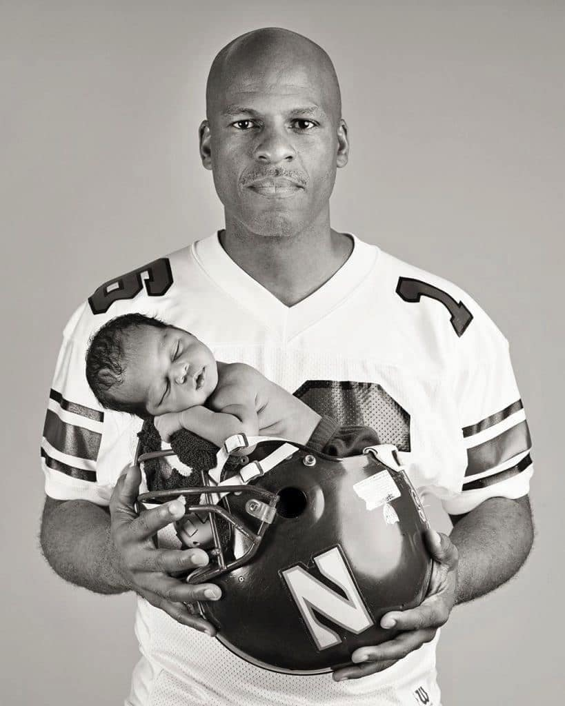 Dad poses with baby in football helmet for a gorgeous personality-filled session