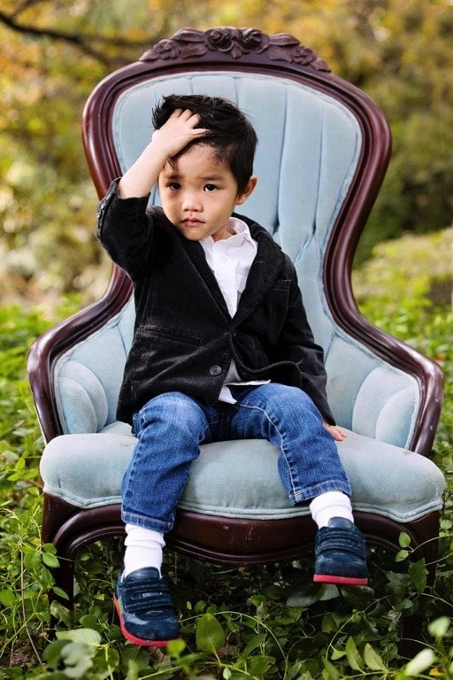 little boy posing on blue chair outside in session