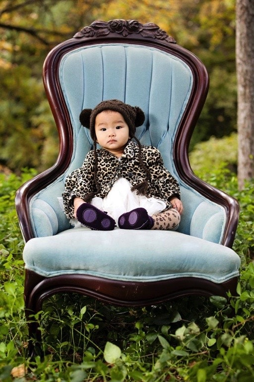 little girl poses in blue chair in a fun hat and jacket