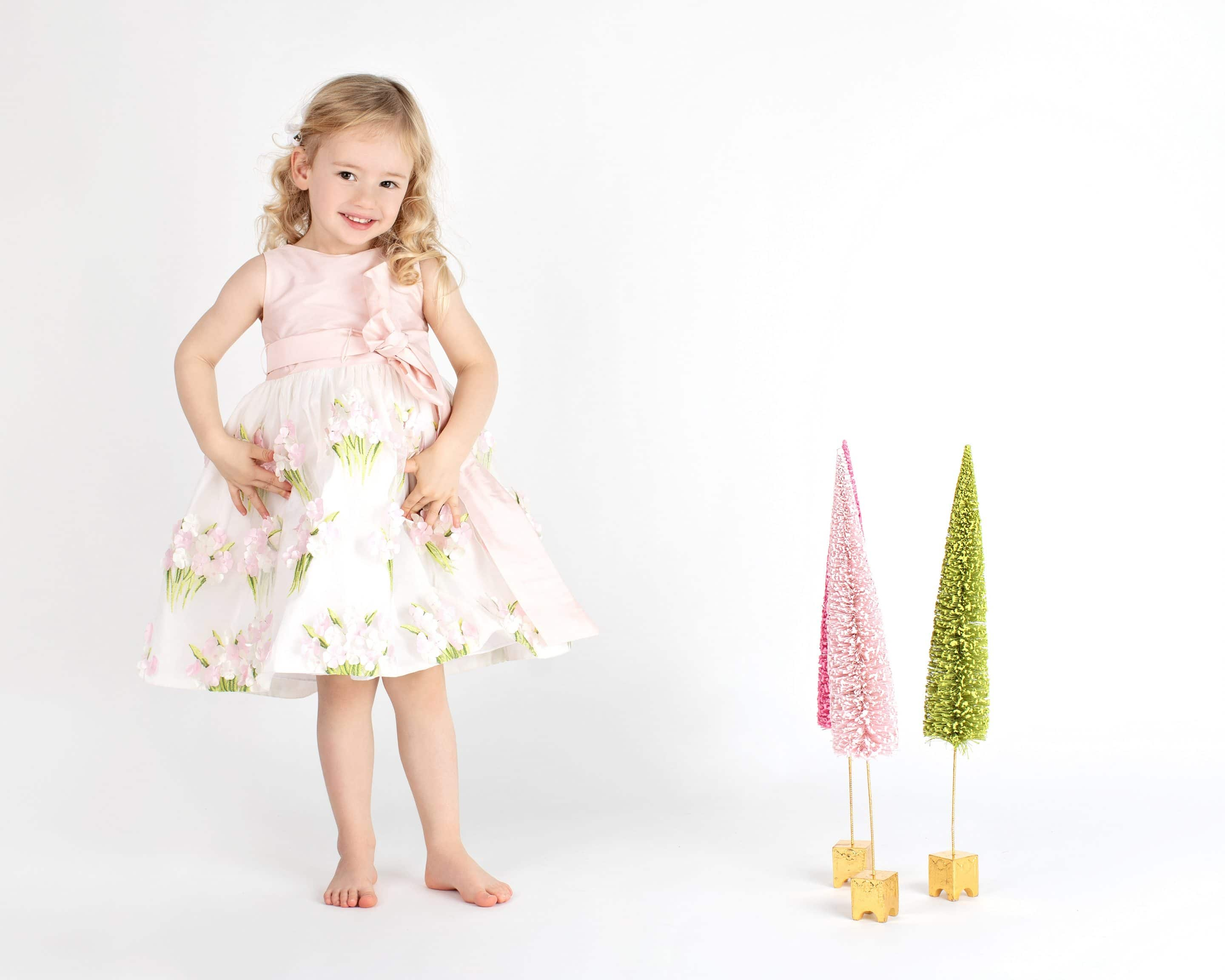 beautiful little girl posing with festive holiday trees