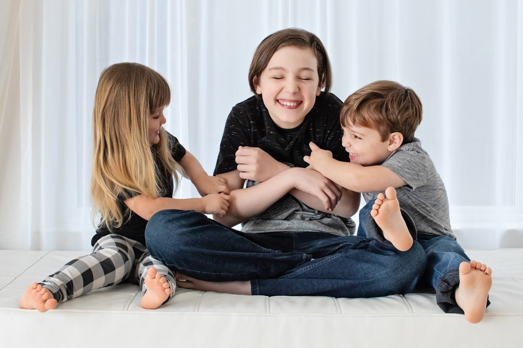 Younger siblings tickling older brother in studio session