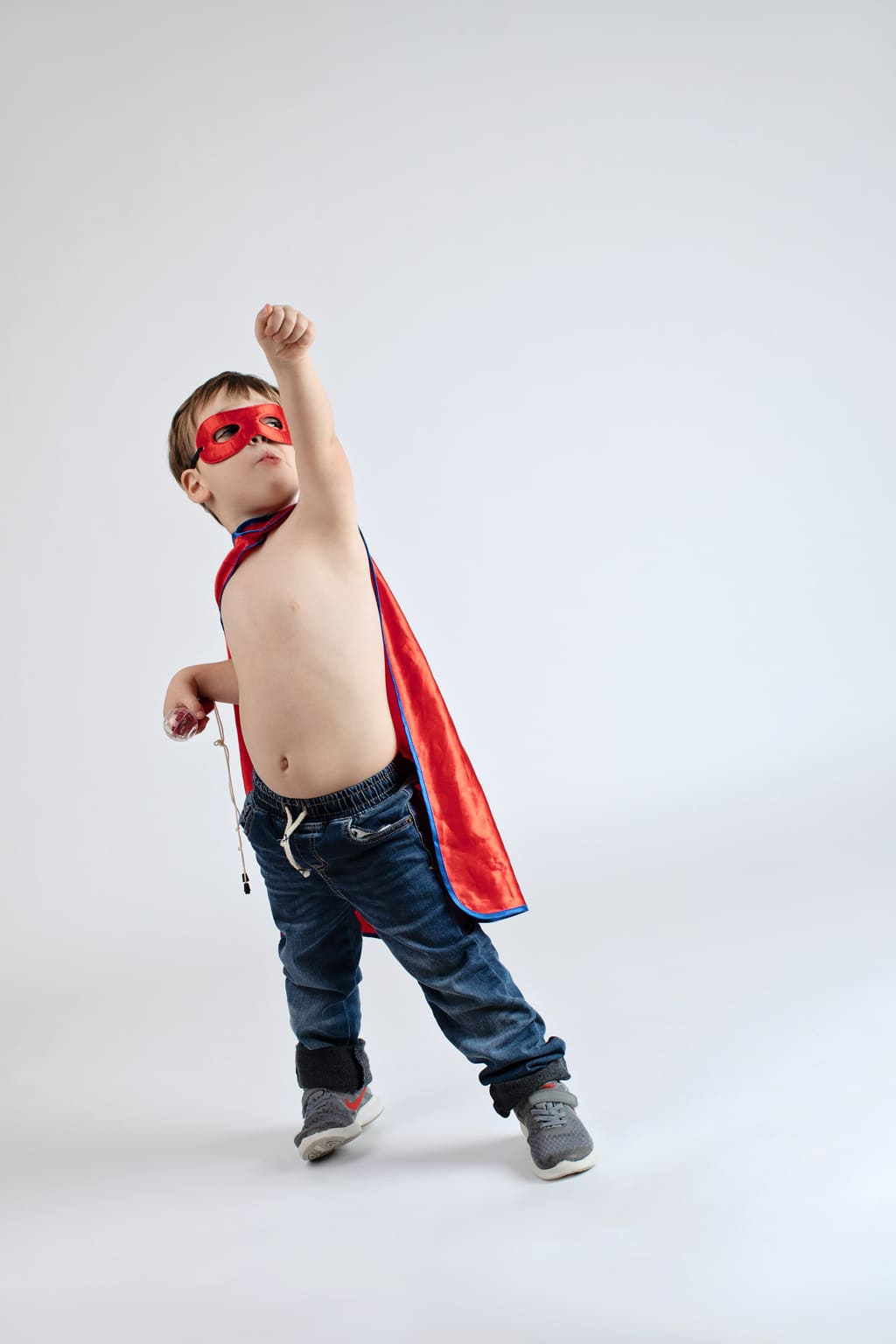 young boy dressed up as superhero plays around in the studio
