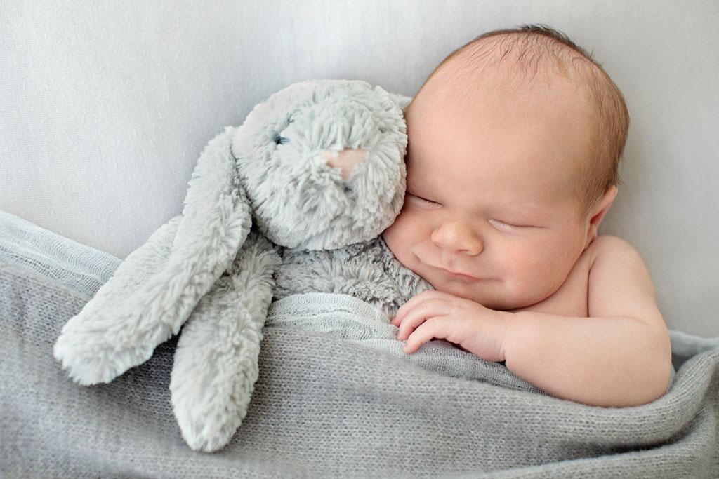 newborn baby boy snuggled up with bunny