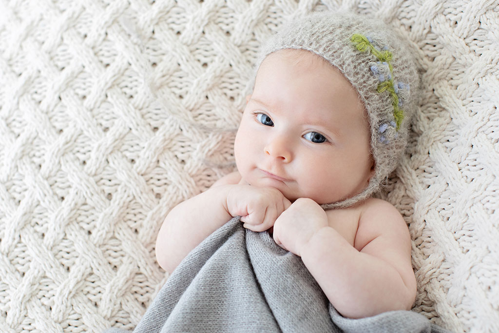 tiny baby girl in knit hat posing in studio