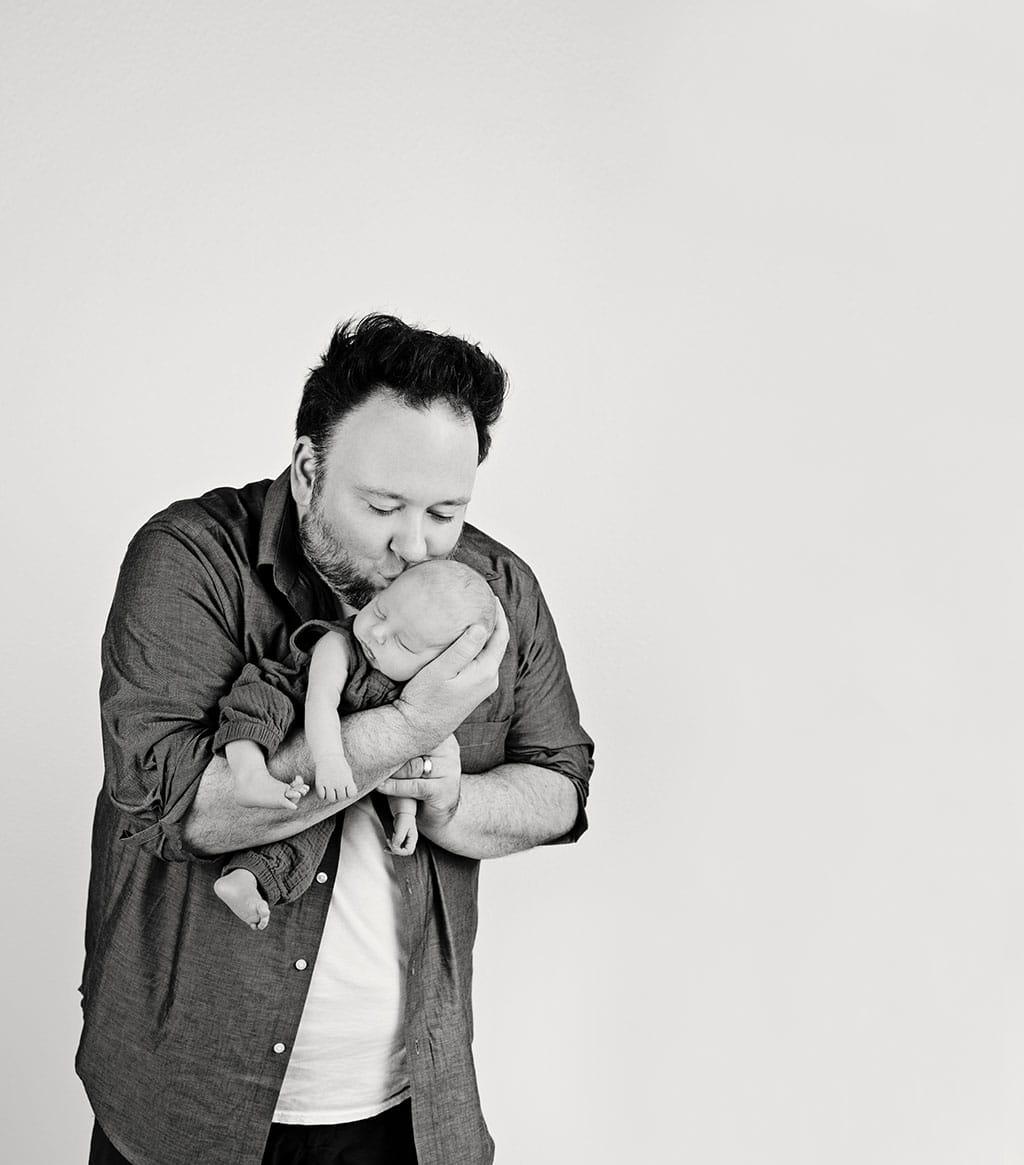 very smitten dad holding newborn baby boy
