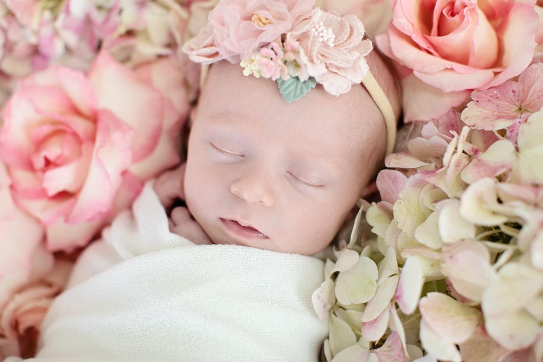 tiny newborn girl in flower bed