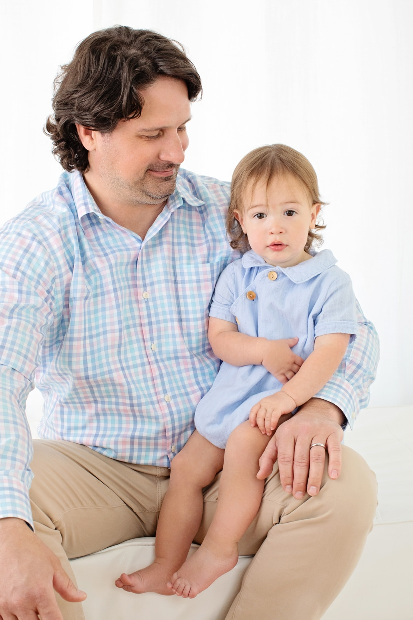 adorable little boy snuggled up with his dad in private studio