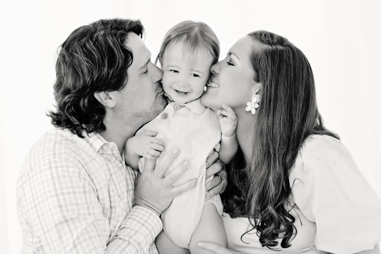 Mom and Dad cozy up with charming little boy